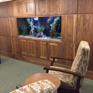 A Wall Mounted Aquarium and Some Chairs Near It